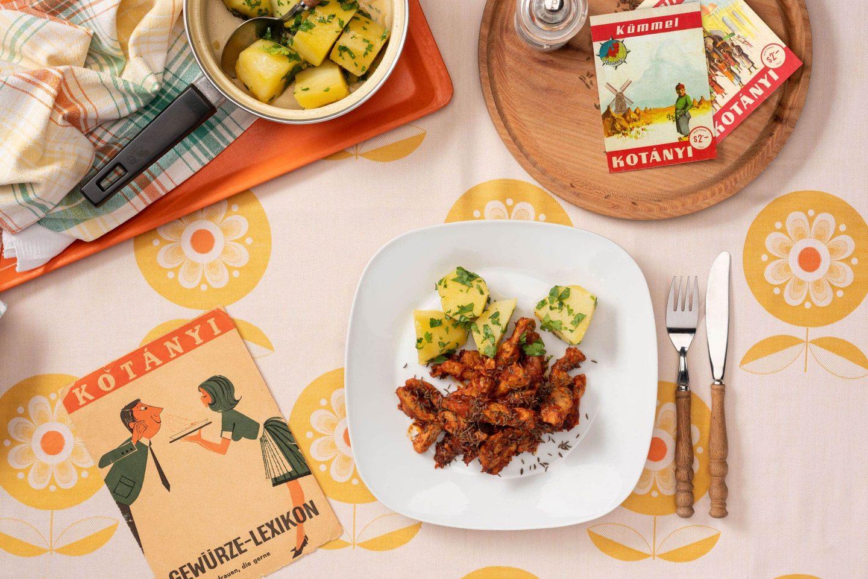 Порція приправленої кмином свинини та картопля з петрушкою на квадратній тарілці.