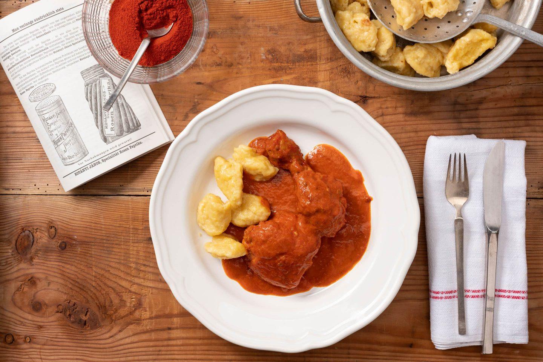 Глибока тарілка з куркою з паприкою та кльоцками, поруч– миска з меленою паприкою.